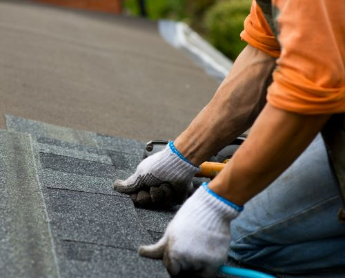 man laying shingles